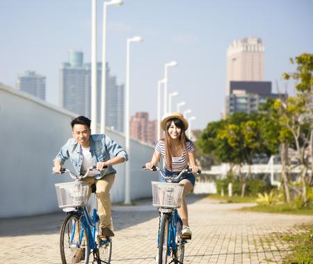 glückliches junges Paar auf dem Fahrrad im Stadtpark Reiten