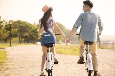 gelukkig jong koppel rijden op de fiets in stadspark Stockfoto