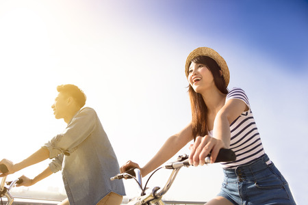 Happy young couple going for  bicycle ride on a sunny day Stock Photo