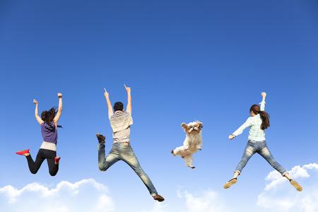 Gelukkig jonge groep springen samen met hond Stockfoto