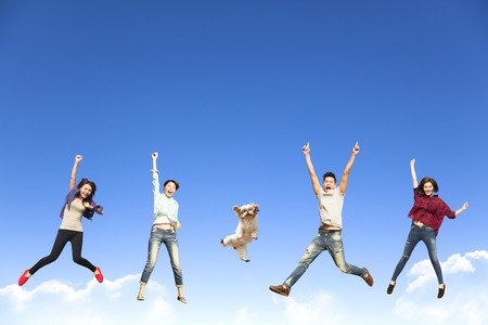 happy young group jumping together with dog