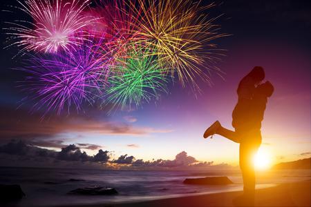 fuegos artificiales: la puesta del sol de la silueta de la joven pareja en el amor que abraza en la playa Foto de archivo