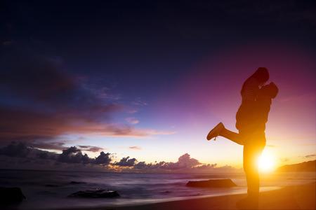 zonsondergang silhouet van jonge paar in liefde knuffelen op strand Stockfoto