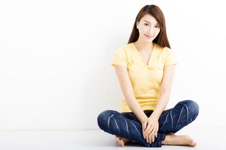 feliz mujer joven sentada en el suelo