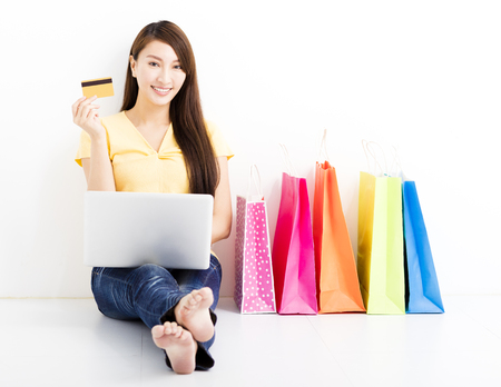 girl with laptop: Smiling  young woman shopping with laptop
