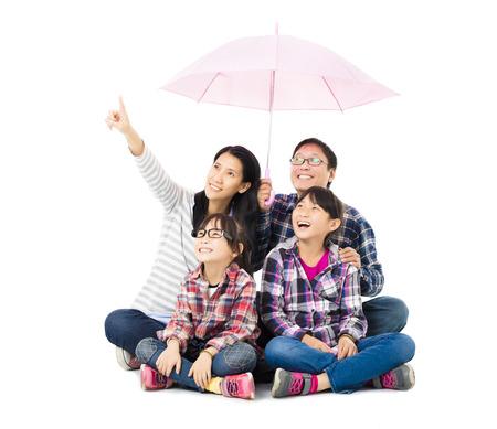 happy family sitting under an umbrella photo