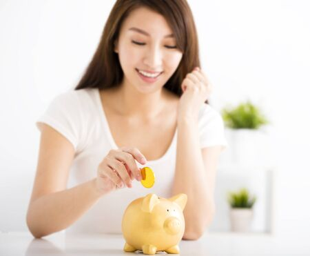 finance girl: Happy young woman Inserting Coin In Piggy bank Stock Photo