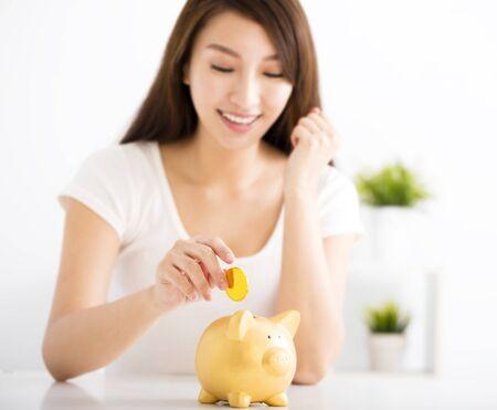 chicas guapas: Mujer joven feliz que inserta la moneda en la hucha