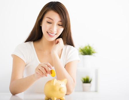 Mujer joven feliz que inserta la moneda en la hucha