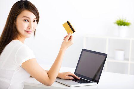 tarjeta de credito: Mujer joven feliz que muestra la tarjeta de crédito y un ordenador portátil