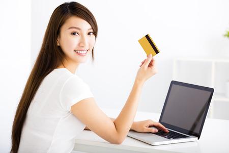 mujeres de espalda: Mujer joven feliz que muestra la tarjeta de crédito y un ordenador portátil