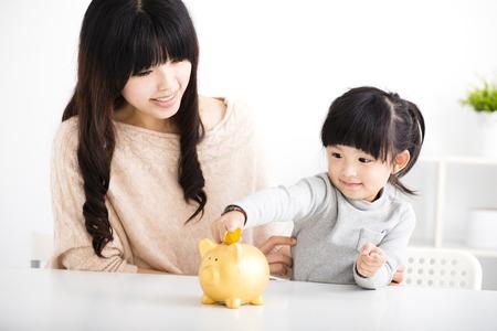 Gelukkige moeder en dochter invoegen muntstuk in spaarvarken