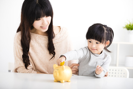 kid smile: Happy mother and daughter Inserting Coin In Piggy bank