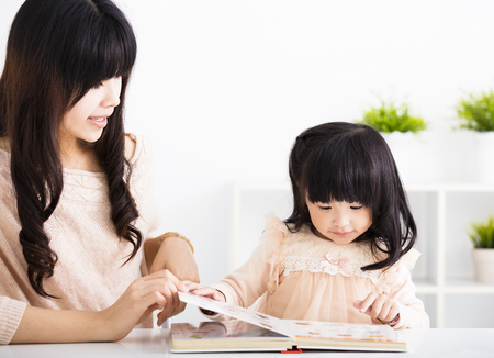 Mother  helping child daughter to reading Zdjęcie Seryjne