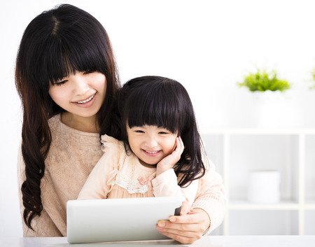 hija: feliz madre e hija que usa la tableta digital en la sala de estar Foto de archivo