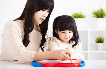 Mother or teacher helping child daughter to writing Stock Photo