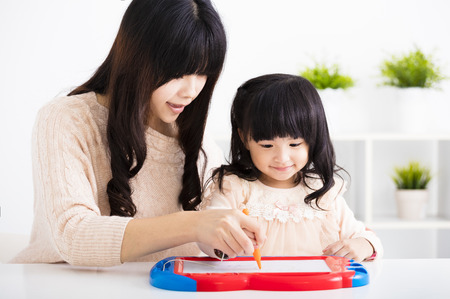 kid book: Mother or teacher helping child daughter to drawing Stock Photo