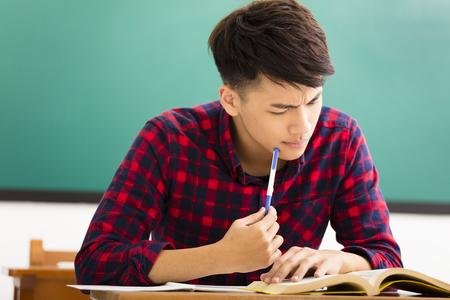 estudiando: Estudiante tensionado que estudia para el examen en el aula