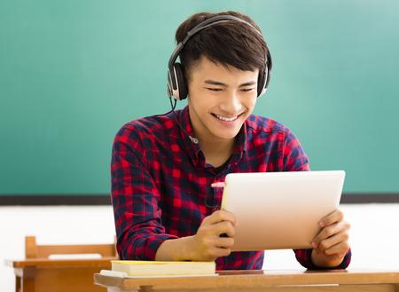 tablilla feliz estudiante de la lectura en el aula