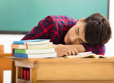 asleep: male Student sleeps on the desk in classroom