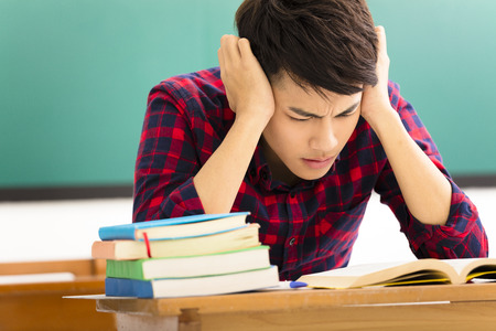 college education: Stressed student  studying for exam in classroom Stock Photo