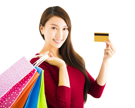 woman holding card: smiling young woman with shopping bags and credit card