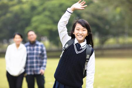 niños saliendo de la escuela: niña linda joven estudiante con los padres en la escuela Foto de archivo