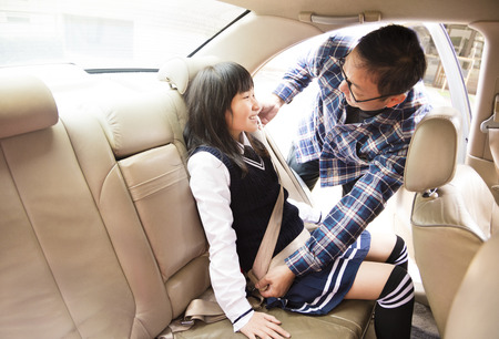 securing: Father securing daughter in the car seat