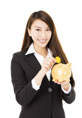 piggy: smiling business Woman inserting coin in  piggy bank
