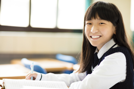 happy pretty  student girl with books in classroom