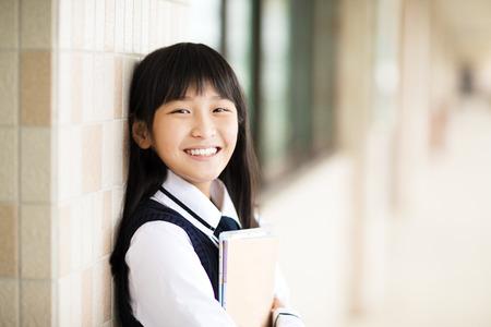 pretty  student girl holding books in front of  classroom Foto de archivo