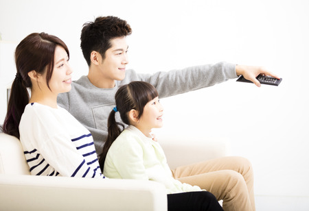 familias jovenes: Feliz atractivo joven de la familia viendo la televisión Foto de archivo