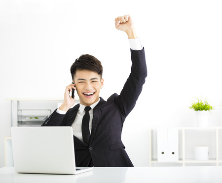 heureux jeune homme d'affaires travaillant dans le bureau