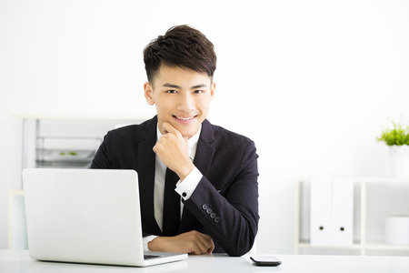young smiling businessman working in office