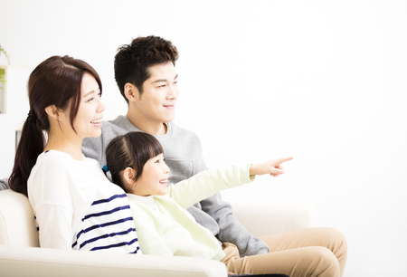 personas viendo television: Feliz atractivo joven de la familia viendo la televisión Foto de archivo