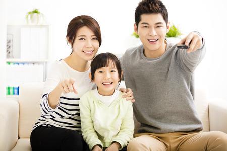 家庭: 快樂有吸引力的年輕家庭觀看電視