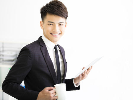man at work: happy young  businessman holding tablet in office Stock Photo