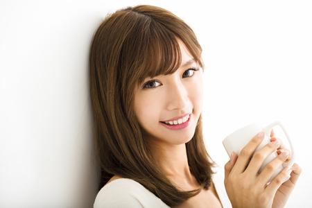 거실에서 뜨거운 라떼 커피를 마시는 젊은 여성
