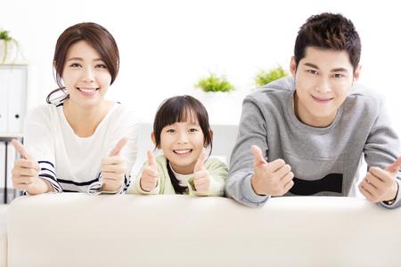 Gelukkig aantrekkelijke jonge gezin met duimen omhoog