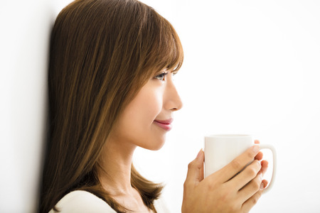 hot drink: young Woman drinking hot latte coffee in living room