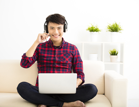 handsome young man using laptop computer with headset