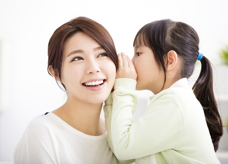 asian child: mother and daughter whispering gossip Stock Photo