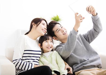家族: ソファの上に selfies を取って幸せな若い家族 写真素材