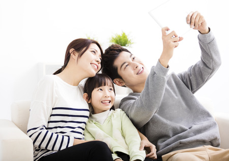 lifestyle: Glückliche junge Familie, die auf dem Sofa selfies