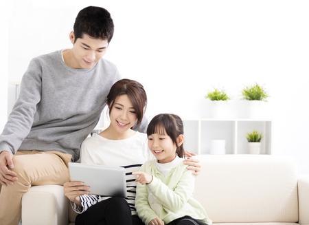 Glücklich attraktive junge Familie, die Tablette beobachten
