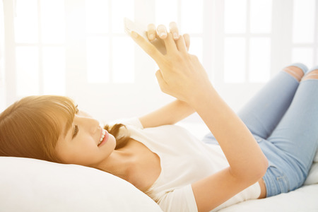 japonais: Young  smile woman reading smart phone on bed