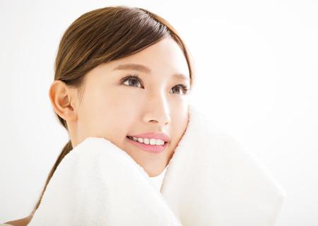 junge Frau, die ihr Gesicht mit Handtuch Reinigung