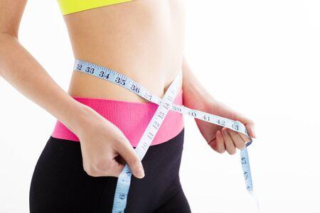 cintura: joven mujer de la aptitud que mide su vientre Foto de archivo
