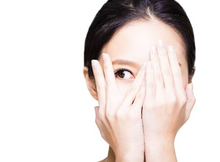 young woman covering her eyes by hands Imagens