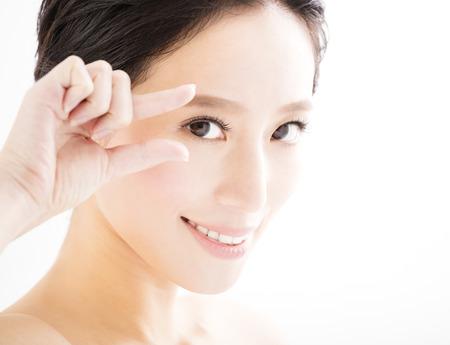 Close-up van jonge glimlachende vrouw ogen met gebaar